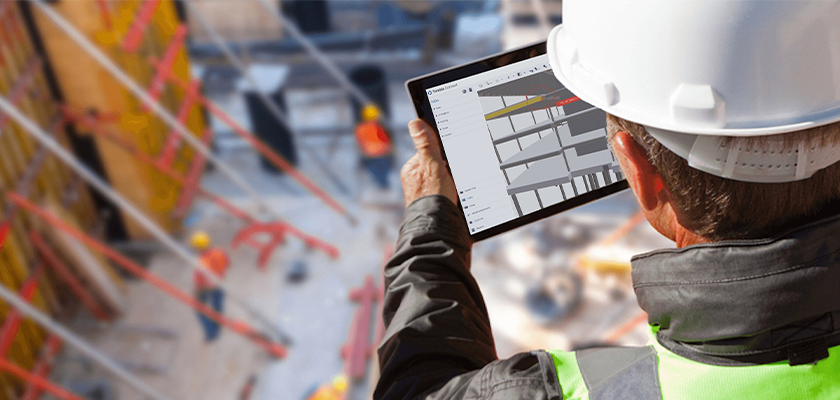 Looking over the shoulder of construction worker holding a tablet with Trimble Connect displaying precast model