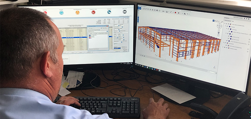 Waring Buildings employee sat at computer, Tekla PowerFab shown on two computer monitors