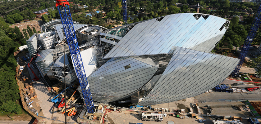 View of Fondation Louis Vuitton under construction from above, shows main glass sail being fitted