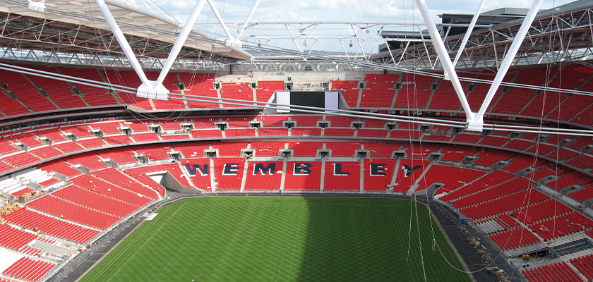 Inside an empty Wembley Stadium, lots of red chairs, blue chairs spell out WEMBLEY