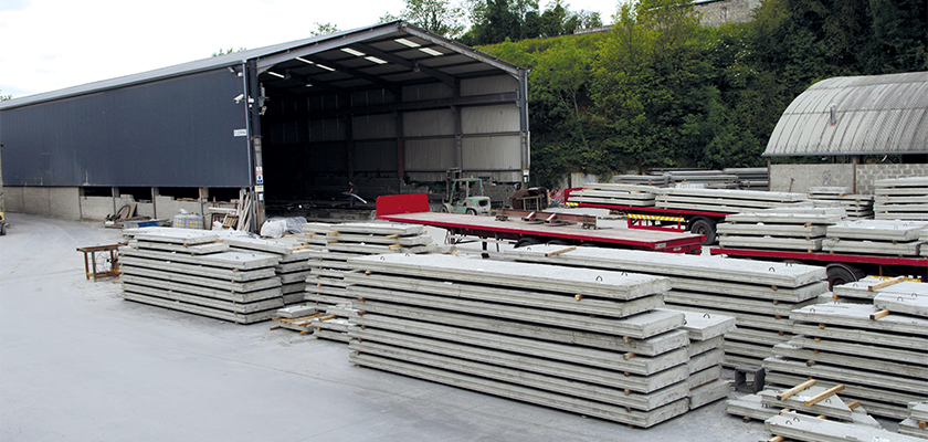 Precast slabs piled in production yard being loaded onto a lorry