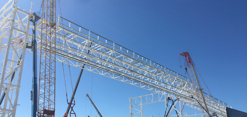 Cranes lift truss from assembly frames