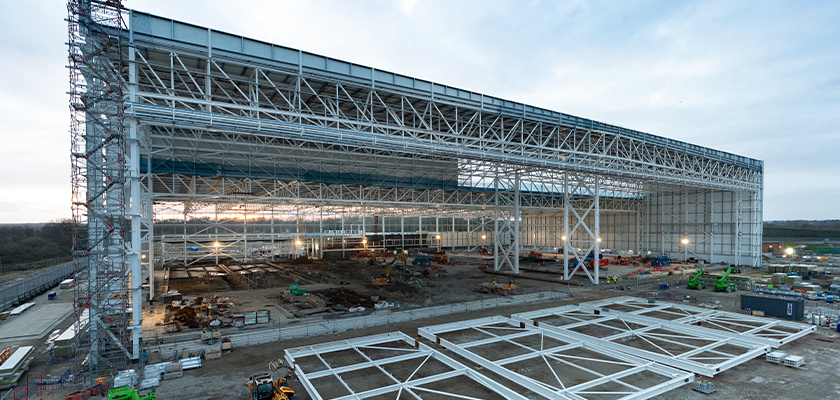 Boeing hanger steelwork with staircase, panels lay on ground ready for assembly in front of hanger