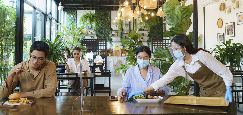 diners and server wearing mask in restaurant