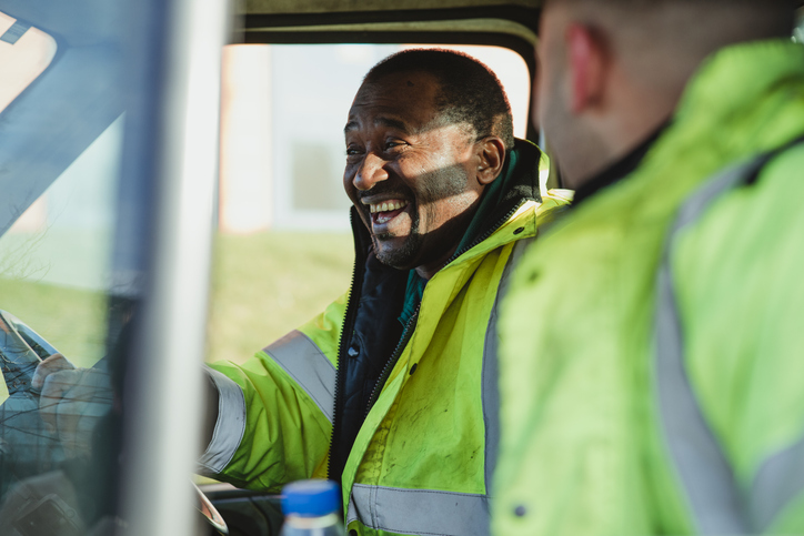 A truck driver who is happy because he enjoys a healthy work-life balance