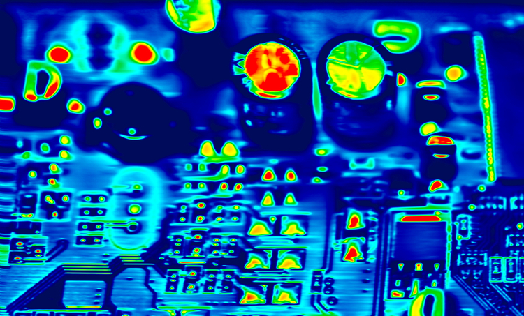 A thermal image of a printed circuit board showing capacitor failure due to repeated thermal cycling
