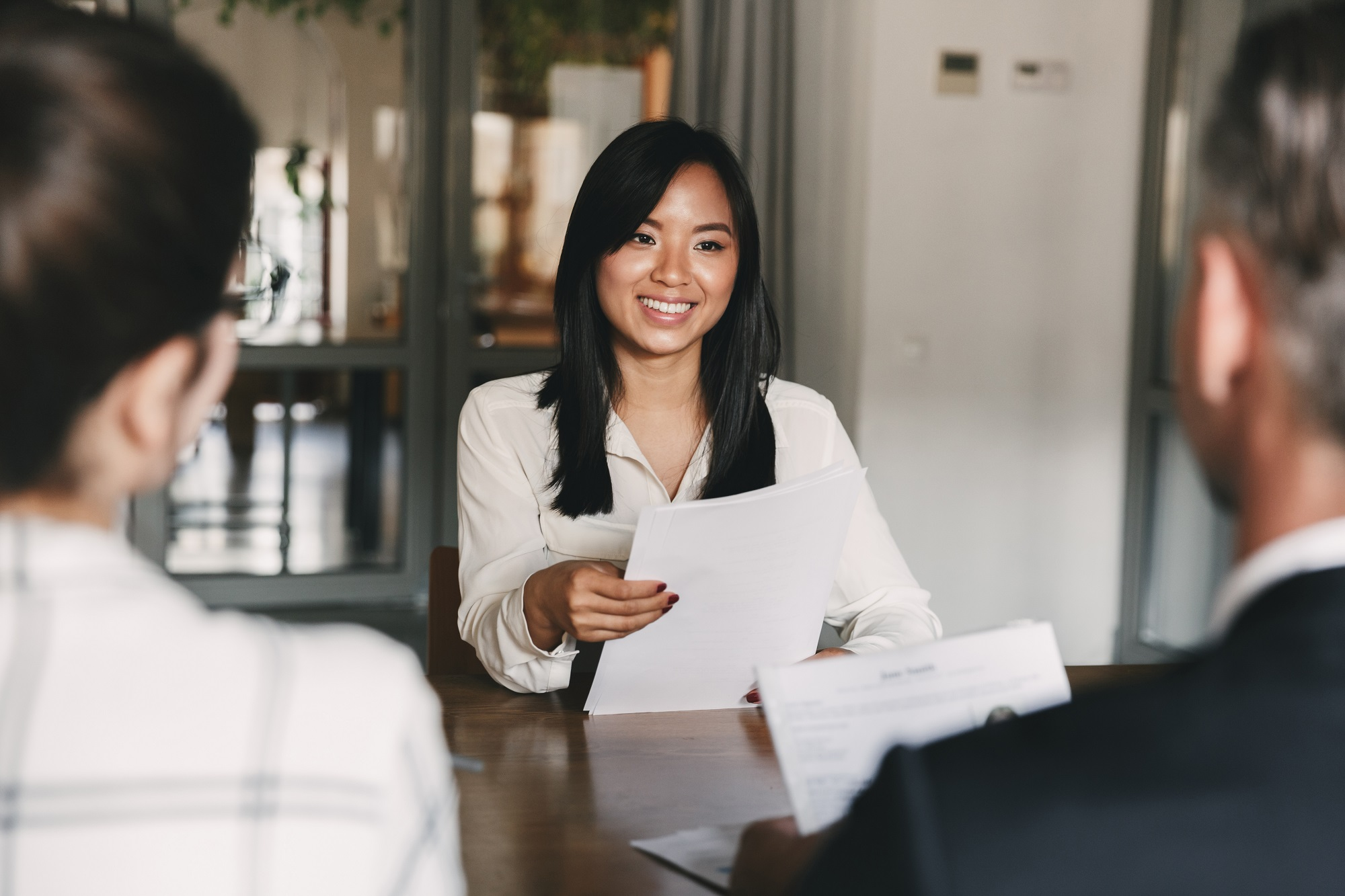 Woman interviewing team members to understand business needs.