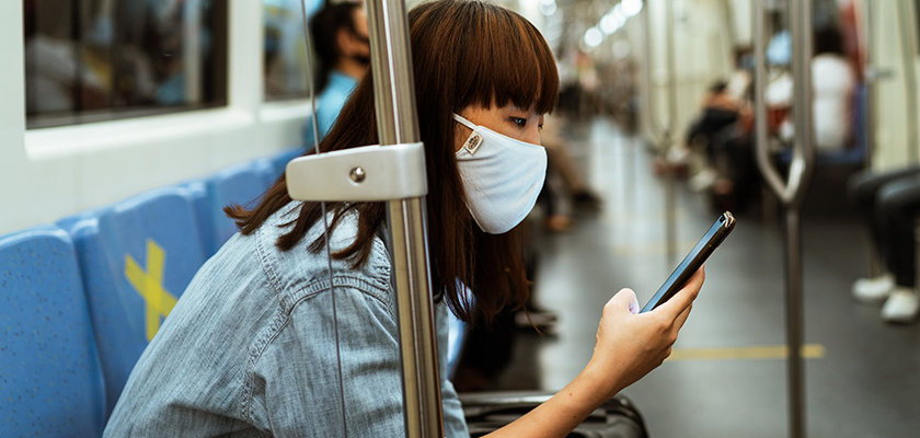 person on bus wearing mask showing new consumer habit