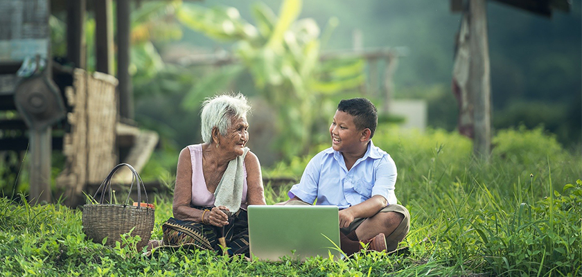 Grandmother and grandson in a field using a computer together