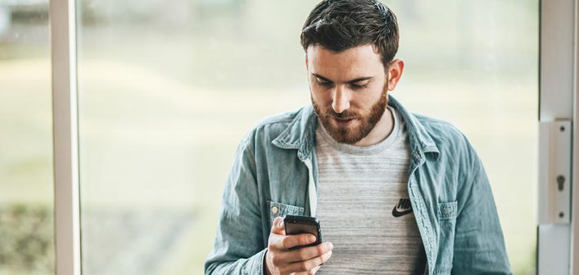 man looking at phone enthusiastically