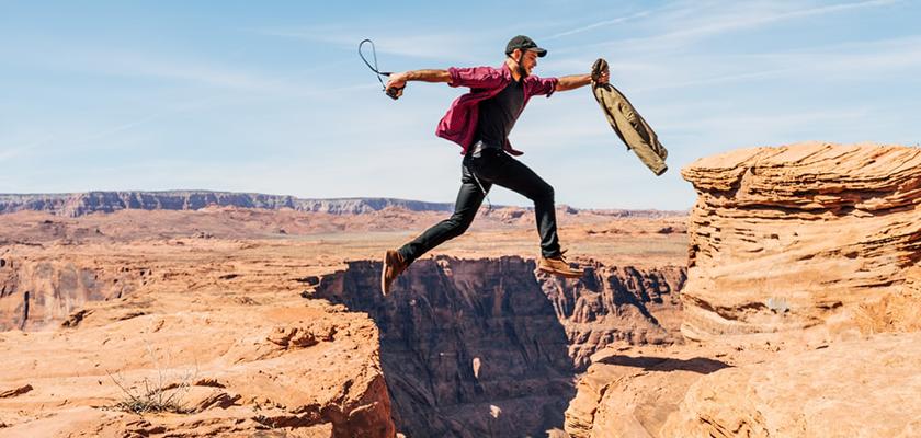person jumping between cliffs