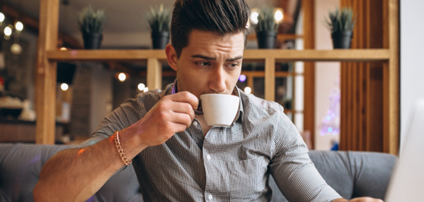 man's consumer habit of drinking coffee while working