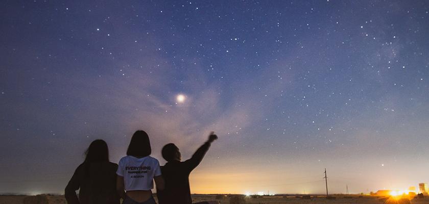 three people stargazing