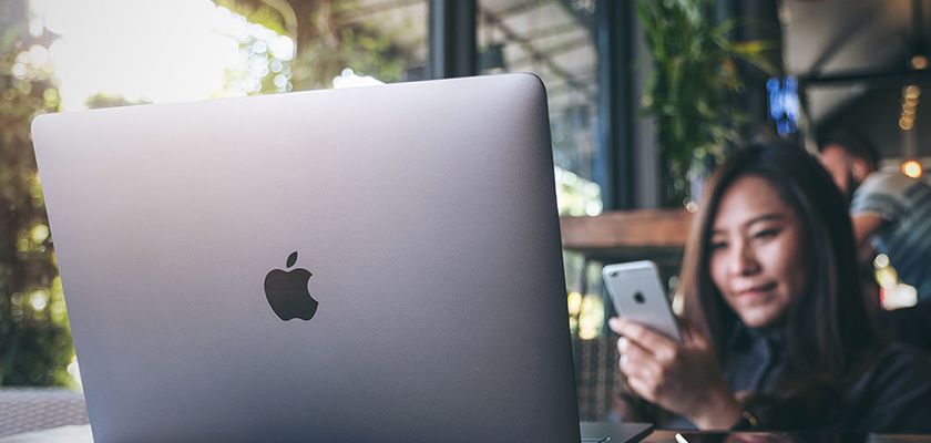 MacBook centered with woman in background on phone