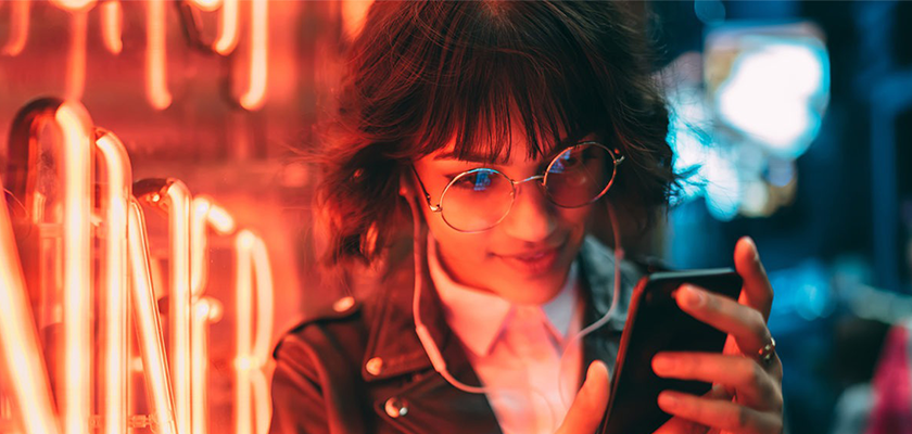 woman looking at her phone with neon lights behind her