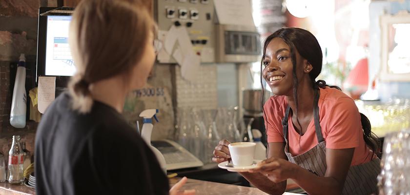 barista handing customer coffee