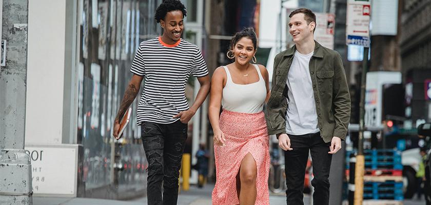 three friends walking down city street while talking