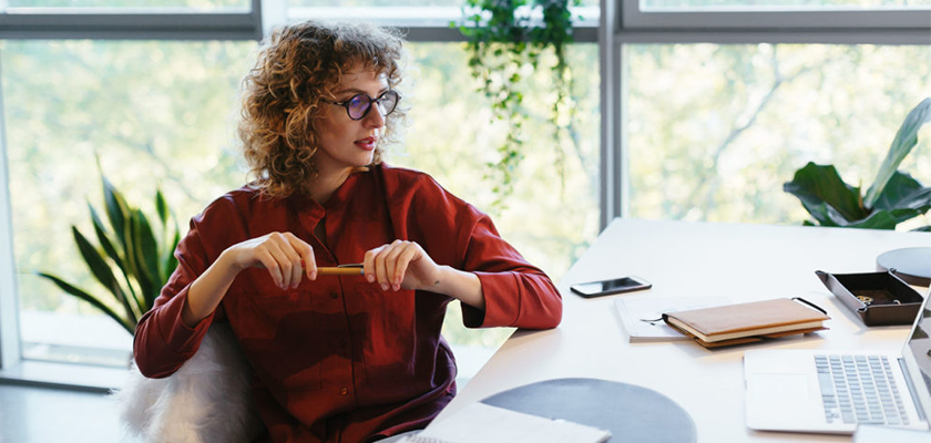 Creative, smart lady sitting at desk with pencil in hand while thinking about strategic planning