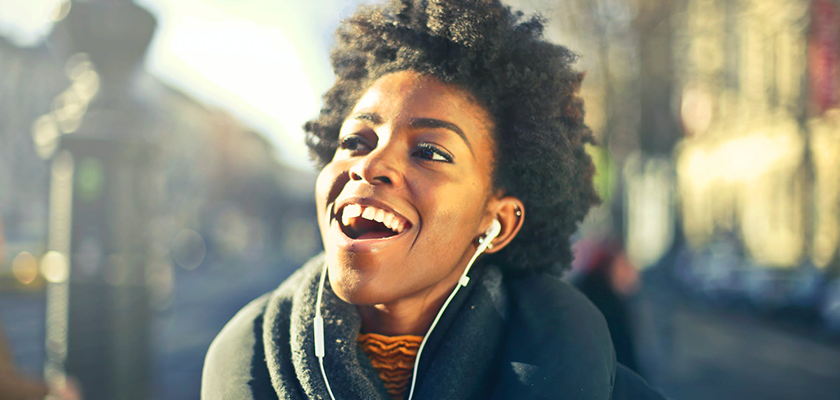 woman listening to music in the Fall while on her way to work