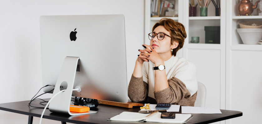 trendy boomer woman anxiously looking at her desktop computer