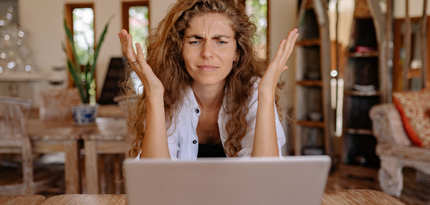 woman looking at computer confused with hands up