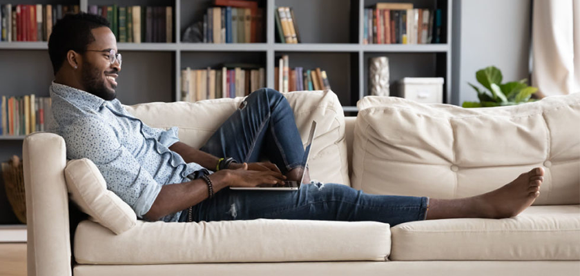 man laying on couch engaging in online community with computer