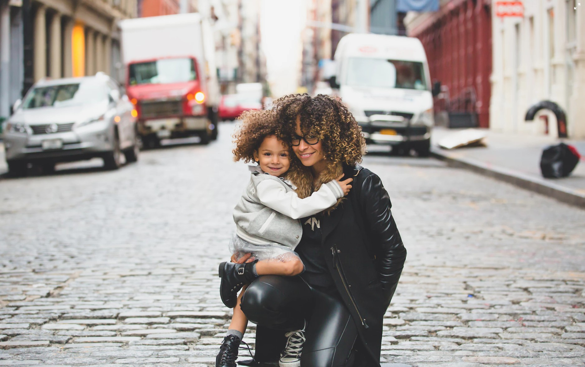 mom and daughter hugging in the street