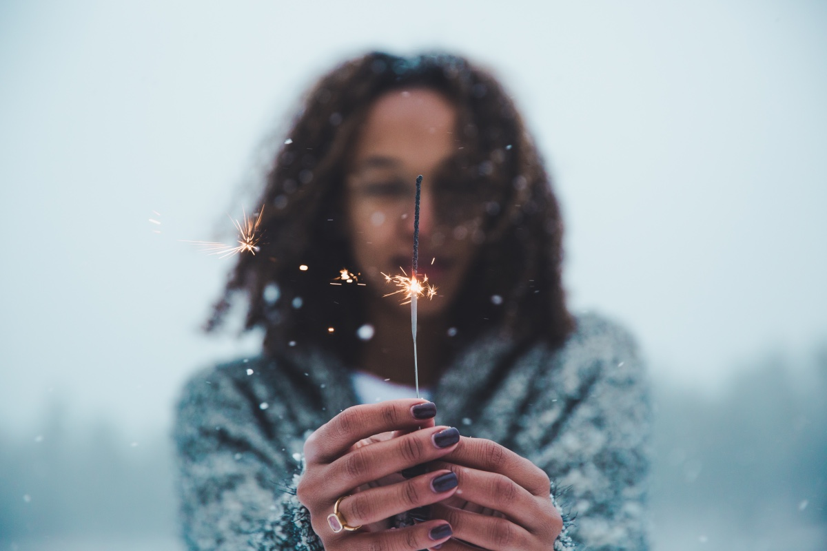 woman on beach holding sparkler