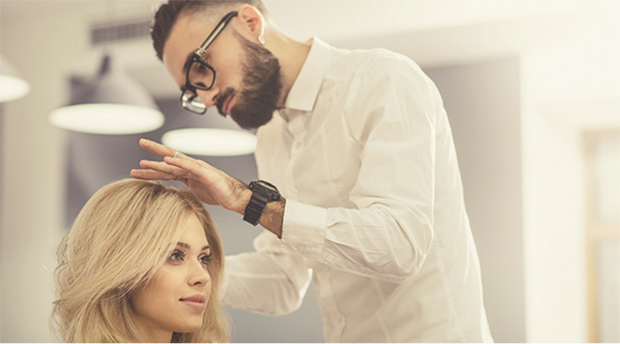 male stylist doing a woman's hair