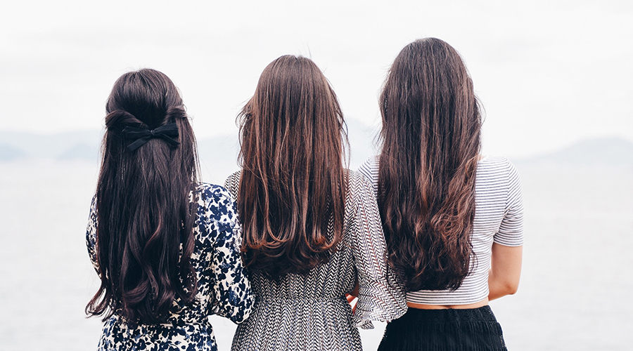 three women standing with brown hair
