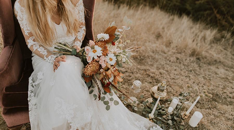 blonde bride sitting in brown velvet chair with bouquet