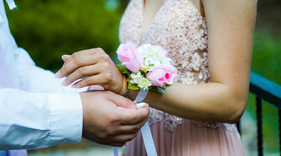 man putting corsage on girl in pink dress for prom