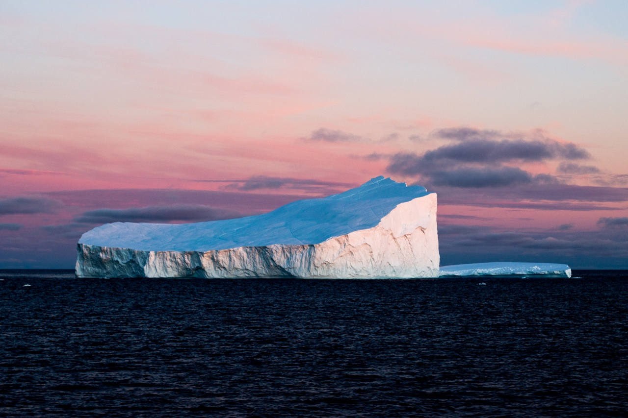 An imposing iceberg in stark contrast to the warm-colored Arctic sky.