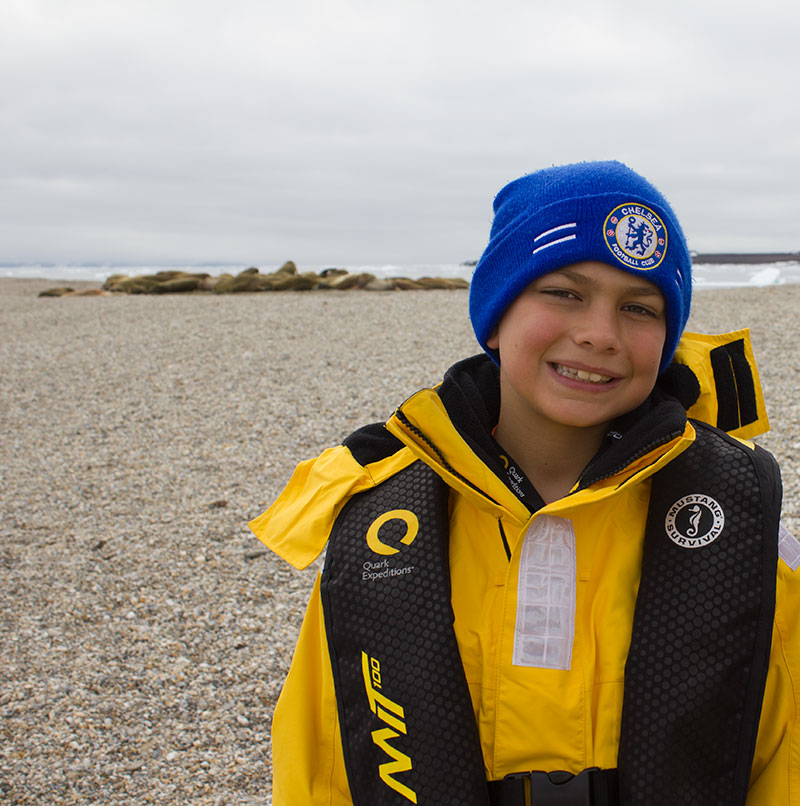 Owen Schuster smiles wide for the camera, a large gathering of walrus hauled out on the Spitsbergen beach behind him.