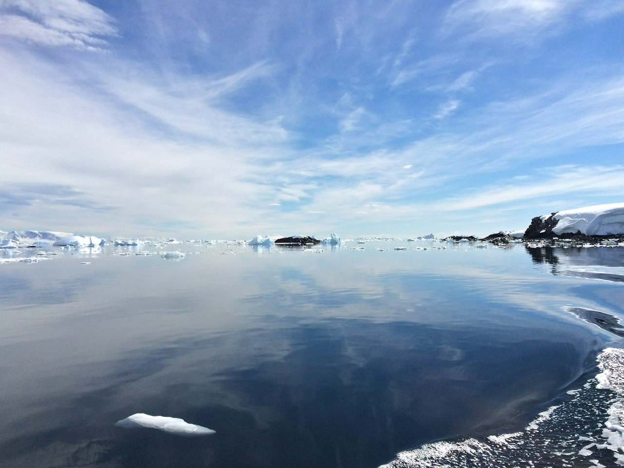 Dreamy blue skies and wispy clouds reflect back over the crystal clear waters of an Antarctic bay, and seen from a cruising Zodiac.