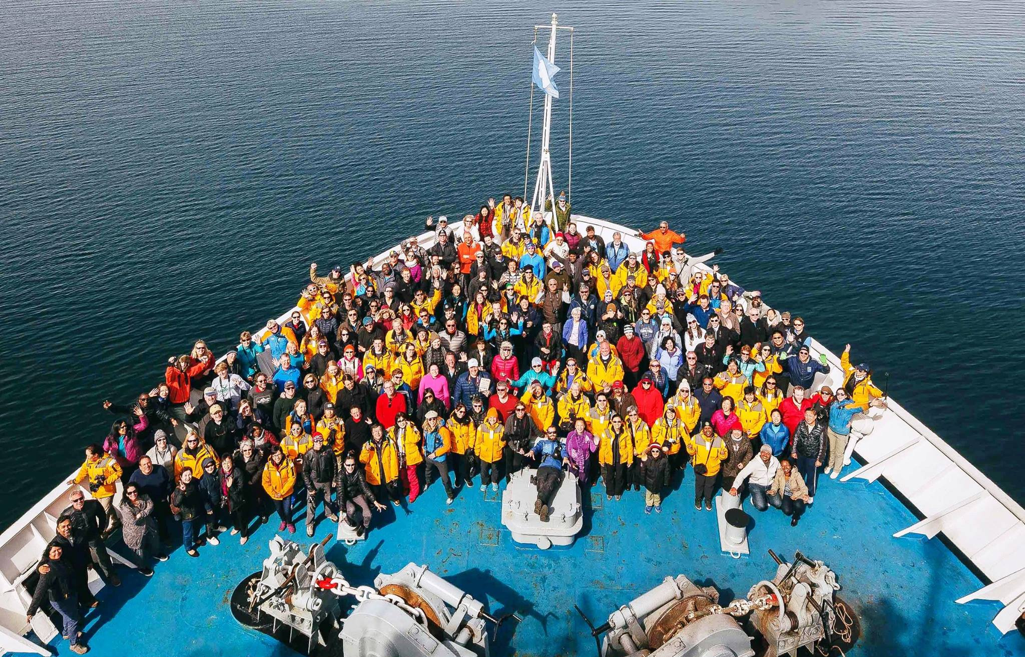 Passengers, crew and expedition team get together for a celebratory group shot on the bow of Ocean Endeavour at the end of their holiday season expedition to Antarctica.