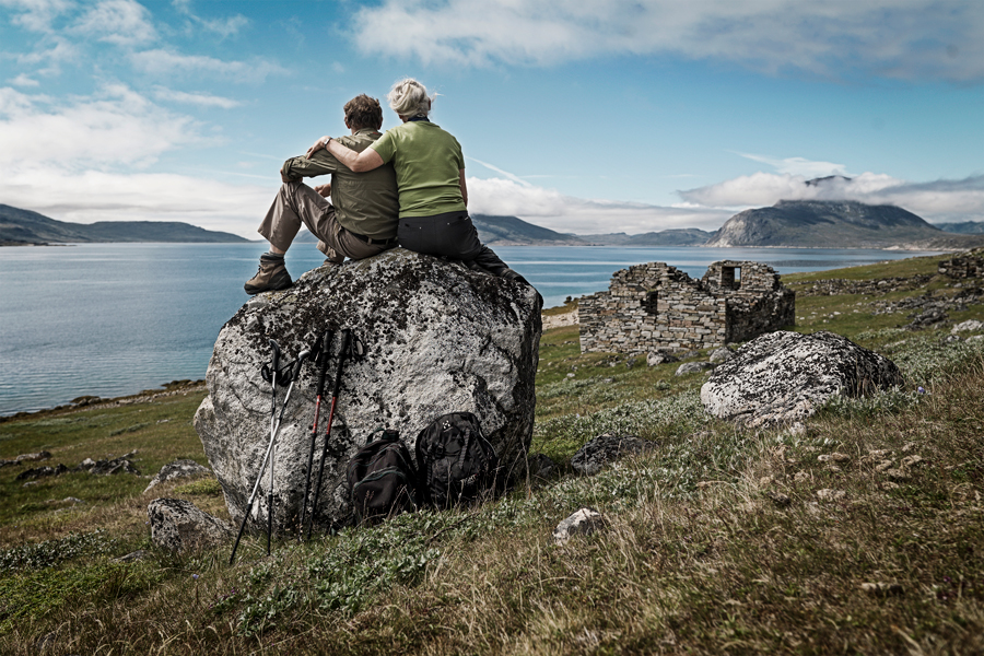A couple enjoy the view from the shores of a Greenland fjord.