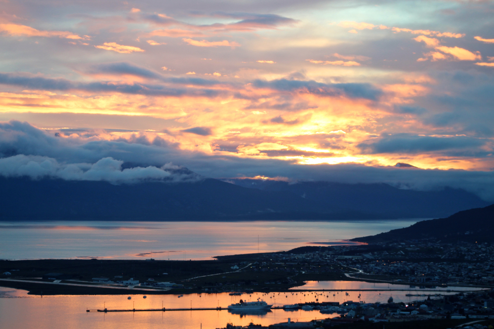 The sun sets over the port of Ushuaia, Aeropuerto Malvinas Argentinas and Beagle Channel; clouds settle in over the Chilean mountains beyond.