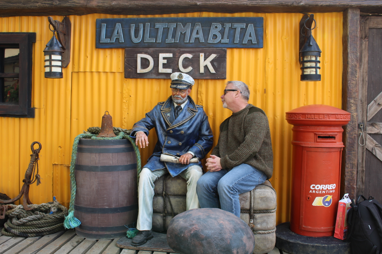 Quark passenger Richard Thomas, on Day One of his Antarctic Explorer: Discovering the 7th Continent expedition, visits the backyard of La Ultima Bita and poses with a life-sized ship's captain figurine on a self-guided tour of downtown Ushuaia.