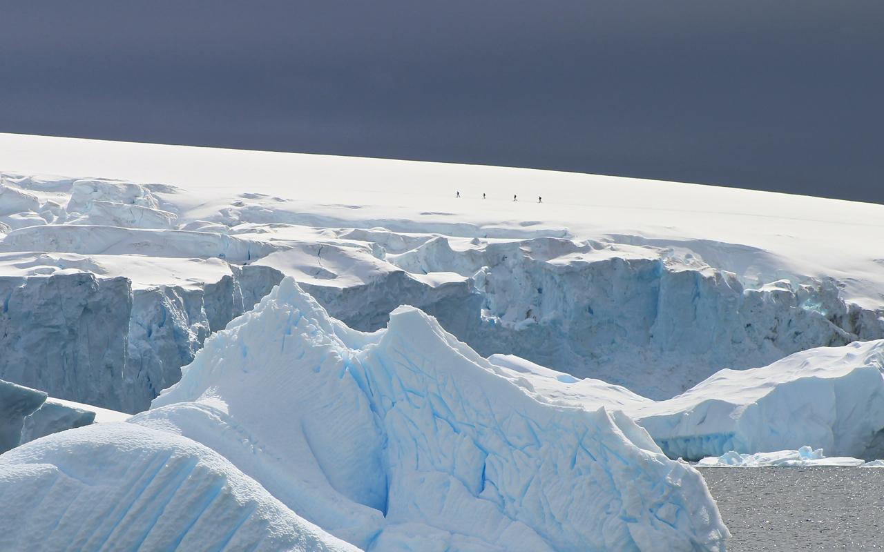 Snowshoers enjoy an exclusive vantage point from high atop a ridge on the Antarctic Peninsula. Photo: Miranda Miller