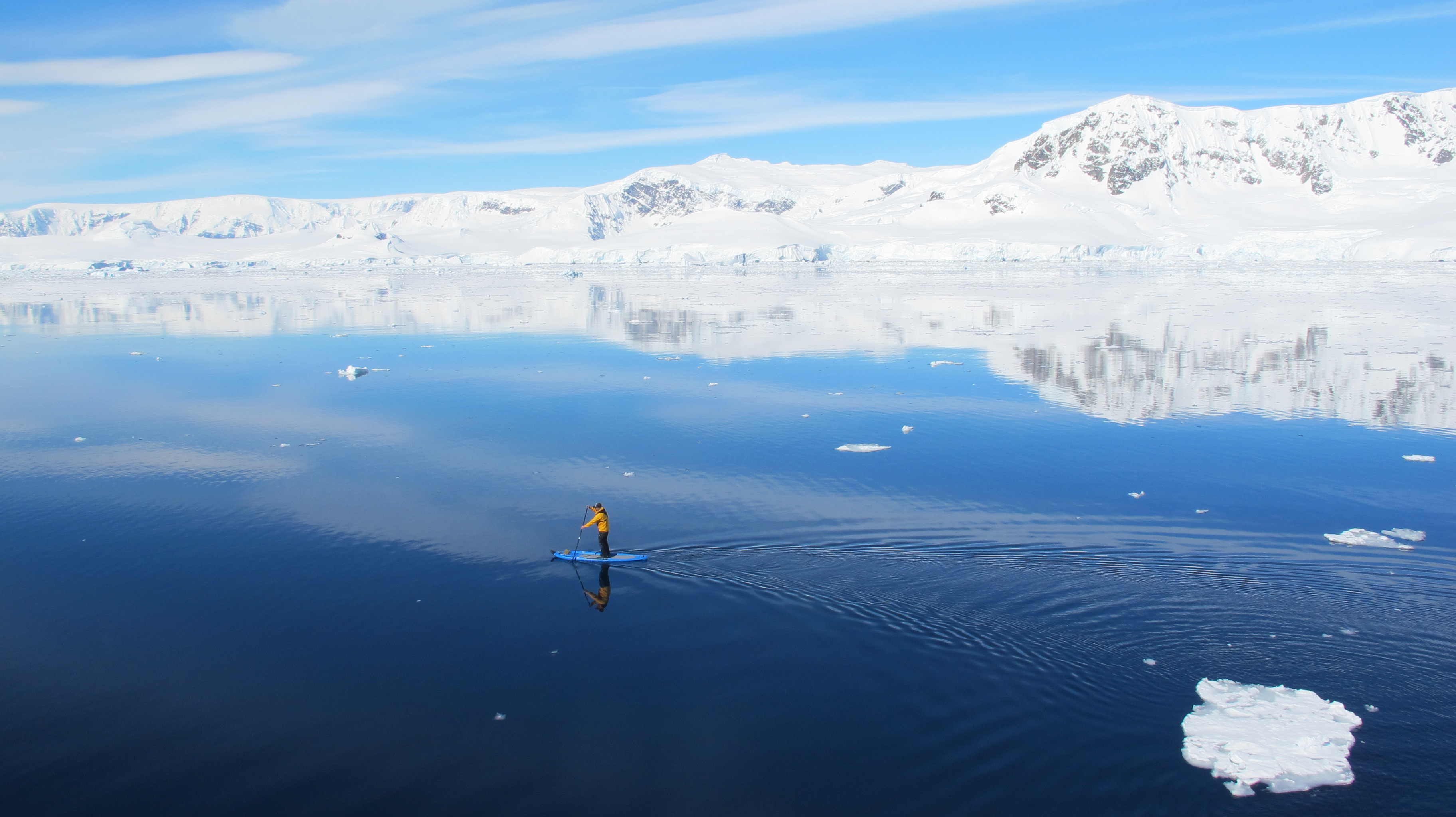 A passenger glides over the surface of pristine, glass-still Antarctic waters on a standup paddleboard.