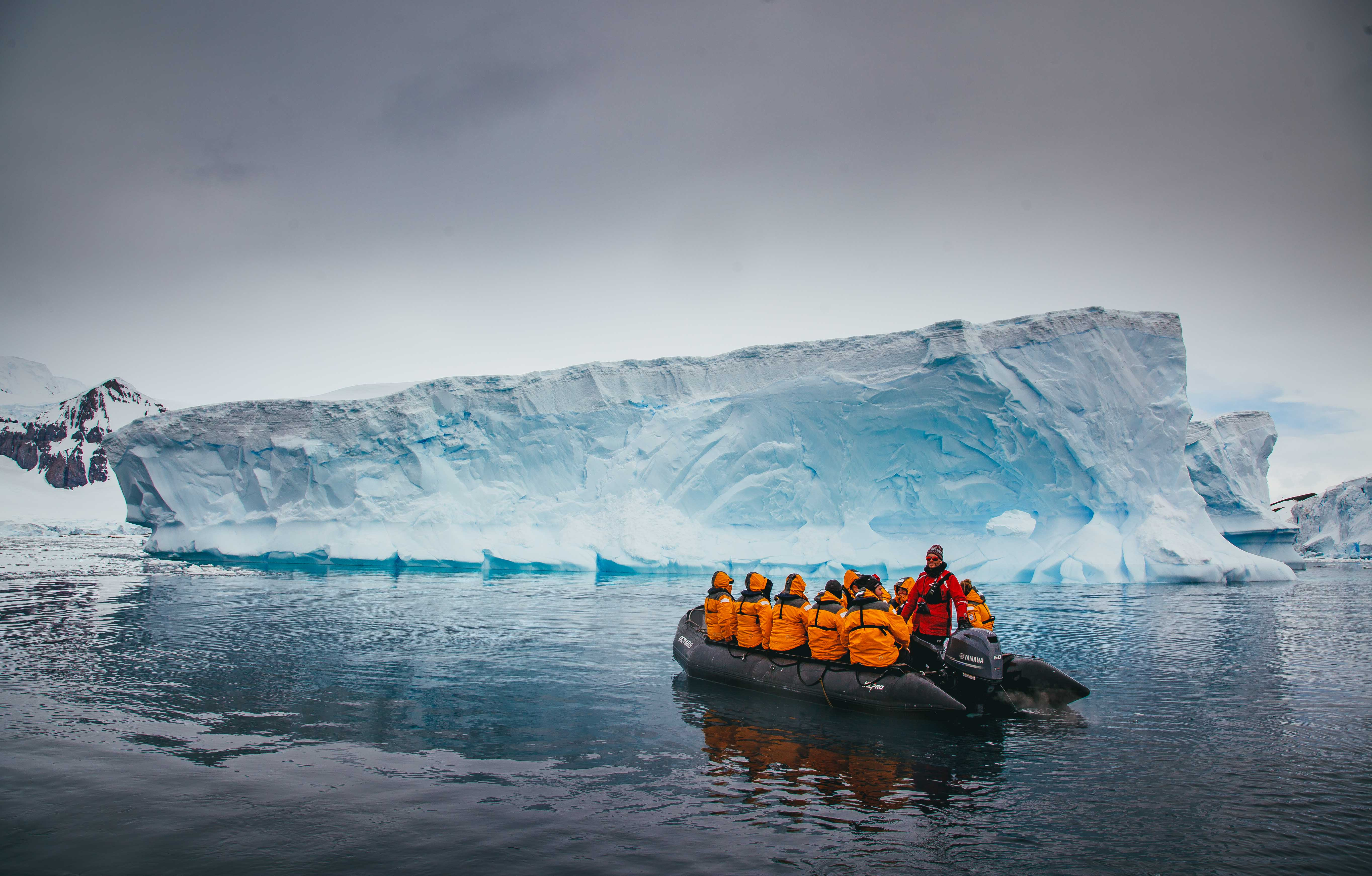 passengers cruise next to iceberg in Antarctica