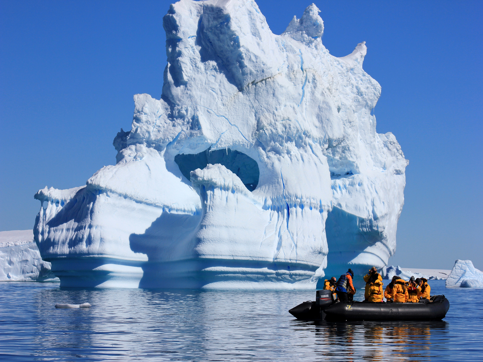 Quark passengers drift by a giant iceberg on a Zodiac excursion in Antarctica.