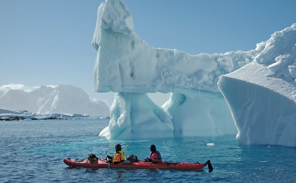 Passengers marvel at a massive iceberg floating nearby while kayaking in Greenland. Photo credit: Keith Perry