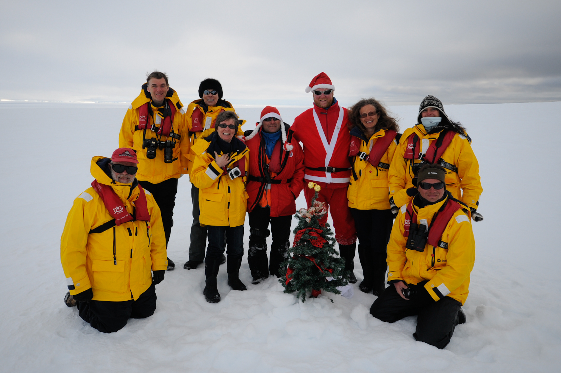Quark Passengers pose with a Christmas tree in Antarctica