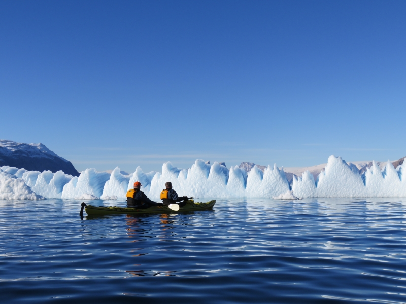 Kayakers take a moment to appreciate a massive wall of ice in their path while on Arctic expedition.