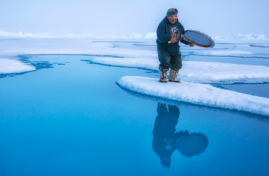 North Pole Summit speaker and Inuit Elder David Serkoak drums on the ice at the North Pole. Photo credit: Cristina Mittermeier
