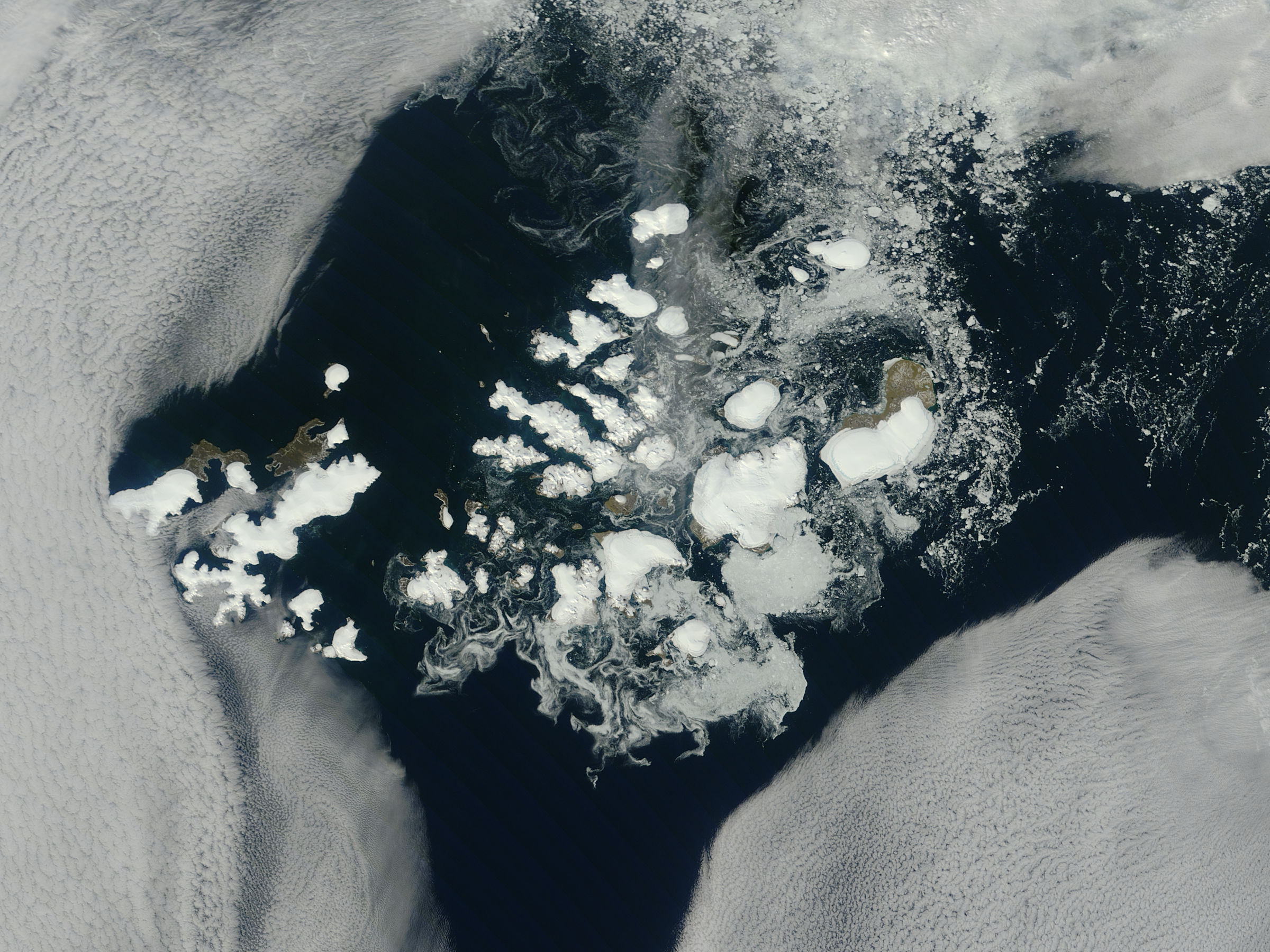 This satellite view of Franz Josef Land through the clouds was captured by the Moderate Resolution Imaging Spectroradiometer on NASA's Terra satellite on August 17, 2011. Photo credit: Jeff Schmaltz, MODIS Rapid Response, NASA Goddard Space Flight Center