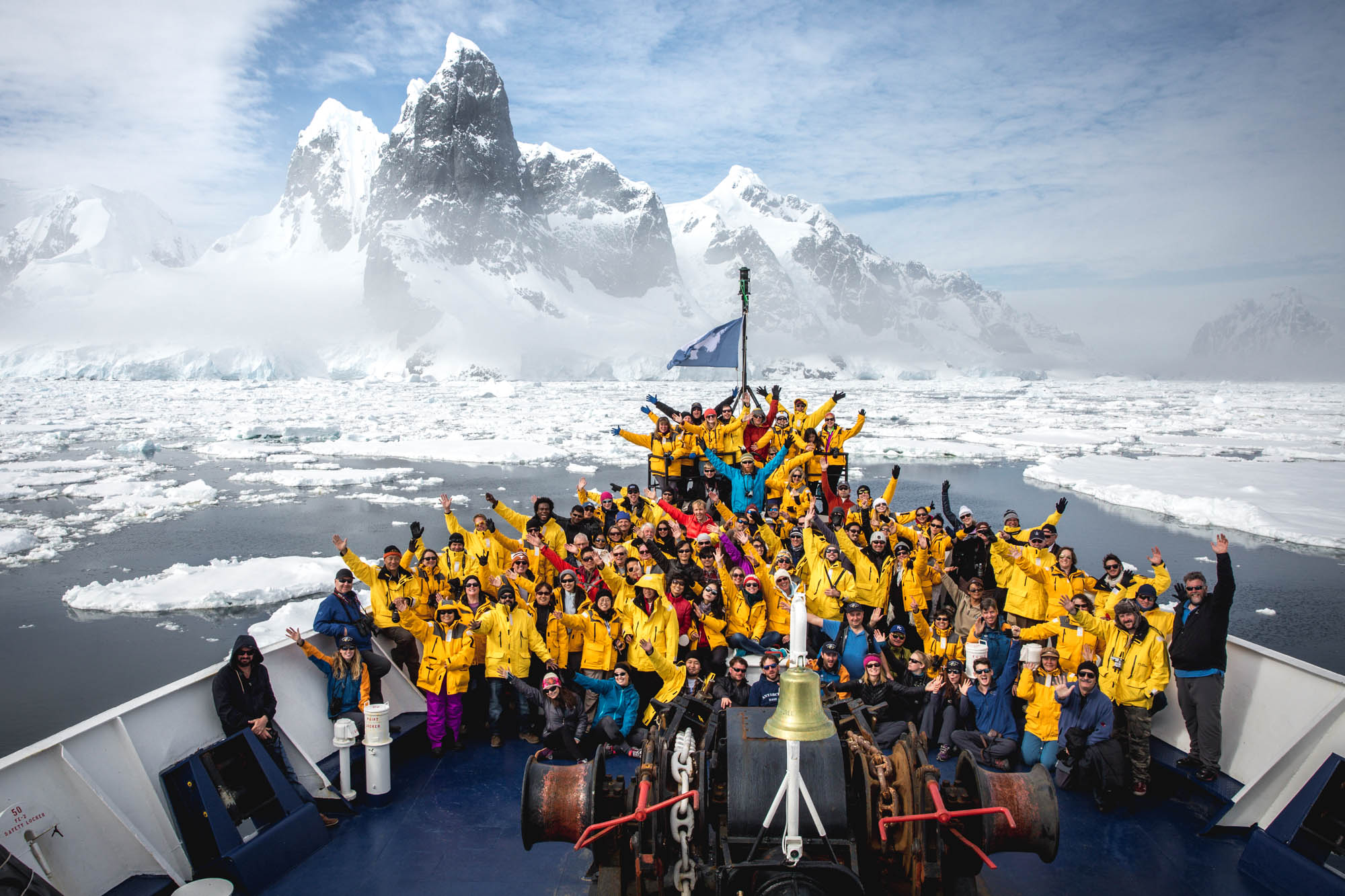 Passengers pose for a group photo on the bow of the ship
