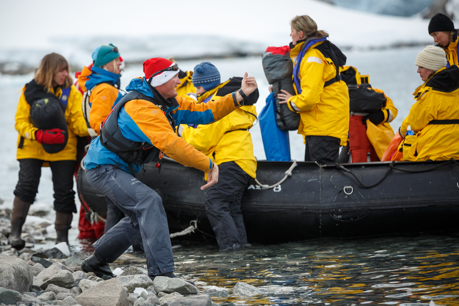 Expedition Team members help passengers disembark zodiacs while on a landing